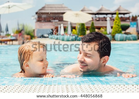 Father and daughter leaning on pool's edge - stock photo