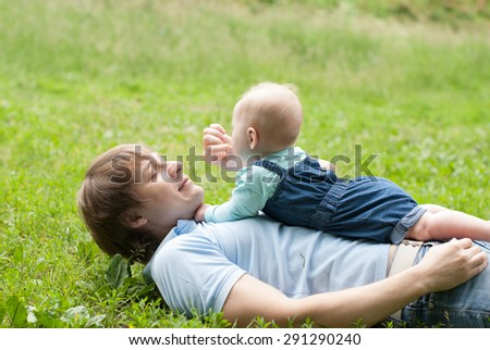 Father and daughter lie on a grass - stock photo