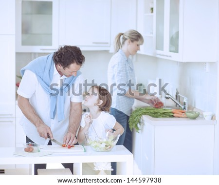 Father and Daughter looking at each other whilst preparing healthy meal in kitchen - stock photo