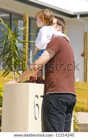 father and daughter looking at their new house - stock photo
