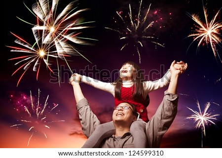 father and daughter looking fireworks in the evening sky - stock photo