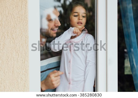 father and daughter looking out the window and smiling