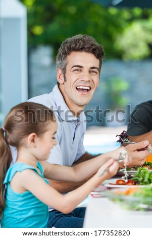 Father and daughter lunch, laughing happy smile eating, sitting at home dinner table - stock photo