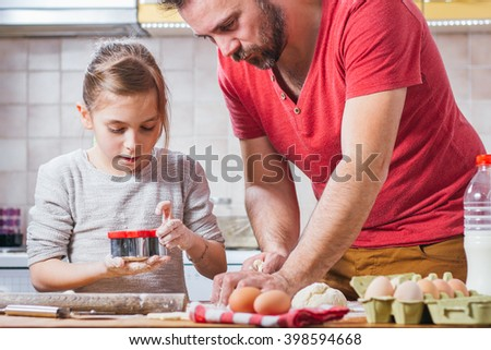 Father and daughter making dough - stock photo