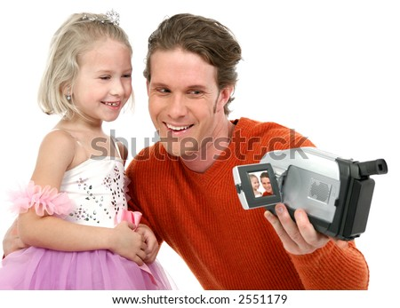 Father and daughter making home videos.  Daughter in ballerina outfit. - stock photo