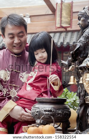 Father and daughter offering incense at the temple in Beijing - stock photo