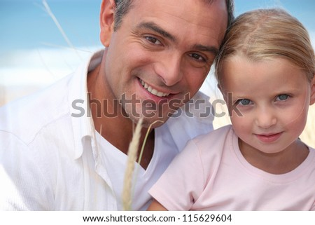 Father and daughter on a beach - stock photo