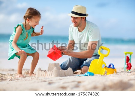Father and daughter on beach building sand castle - stock photo