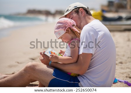 Father and daughter on the beach near the sea. Young man hugs little baby girl and reads her a book - stock photo