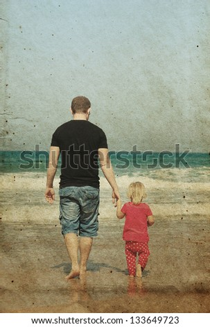 father and daughter on the beach. Photo in old image style.