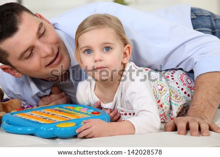Father and daughter playing a game - stock photo