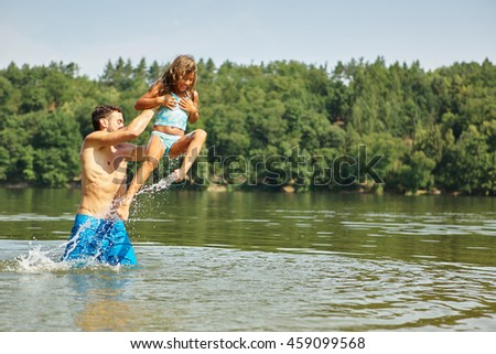 Father and daughter playing and splashing at the lake in summer