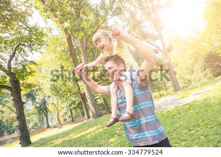 Father and daughter playing at park in New York. The man is carrying the little girl on his shoulders holding her hands. They are looking away from camera. Summer, family and lifestyle concepts - stock photo