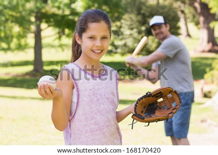 Father and daughter playing baseball in the park - stock photo