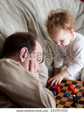 Father and daughter playing chess. - stock photo