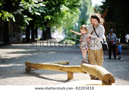 Father and daughter playing in the park at summer - stock photo