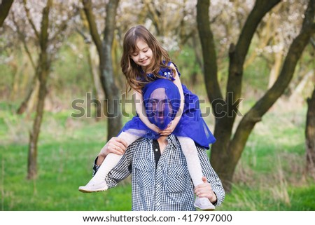 Father and daughter playing in the park. Daughter to sit neck dad. - stock photo