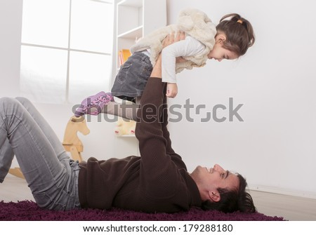 Father and daughter playing in the room - stock photo