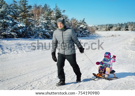 Father and daughter playing in winter on snow