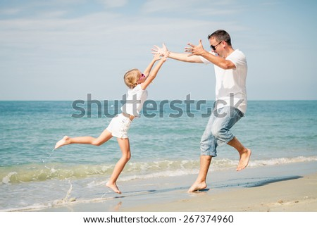 Father and daughter playing on the beach at the day time. Concept of friendly family.