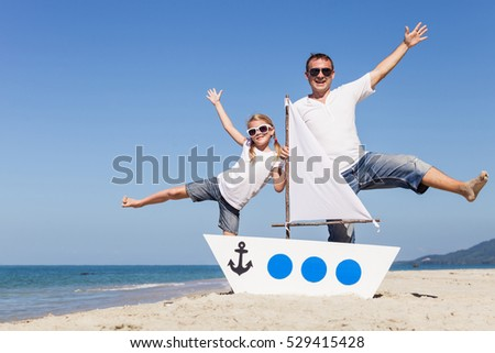Father and daughter playing on the beach at the day time. Concept of happy friendly family.