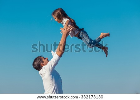 father and daughter playing on the beach at the day time.  fly. - stock photo
