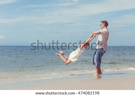 Father and daughter playing on the beach at the day time. People having fun on nature. Concept of friendly family.