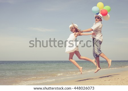 Father and daughter playing on the beach at the day time. People having fun on the nature. Concept of friendly family.