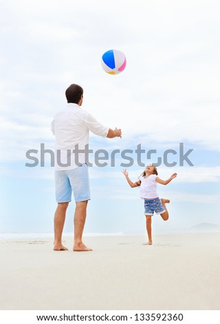 Father and daughter playing on the beach together having fun with beachball - stock photo