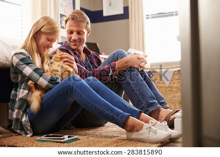 Father and daughter playing with pet cat - stock photo