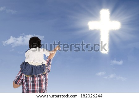 Father and daughter pointing at cross on the blue sky - stock photo
