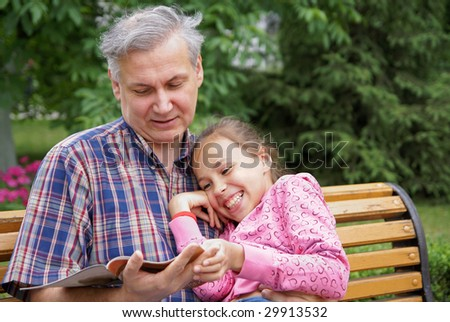 Father and daughter reading a book in park - stock photo