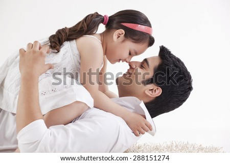 Father and daughter rubbing noses - stock photo