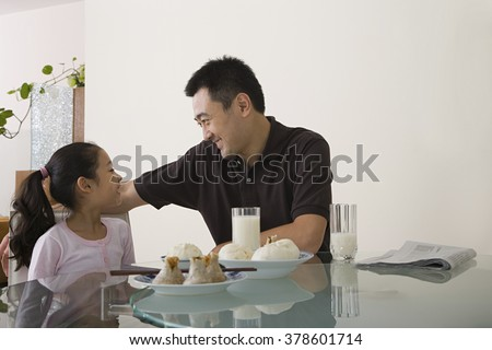 Father and daughter sat at a table - stock photo