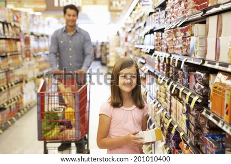 Father and daughter shopping in supermarket - stock photo