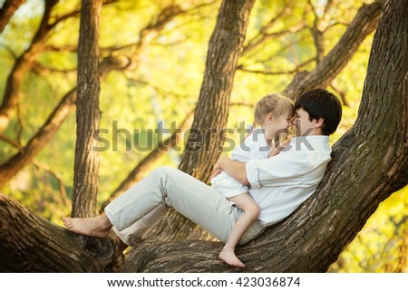 father and daughter sitting on a tree and laughing in the summer garden, happy family - stock photo