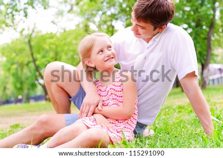 Father and daughter sitting together on the grass, and spend time with family - stock photo
