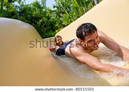 Father and Daughter Sliding Down Water Slide - stock photo