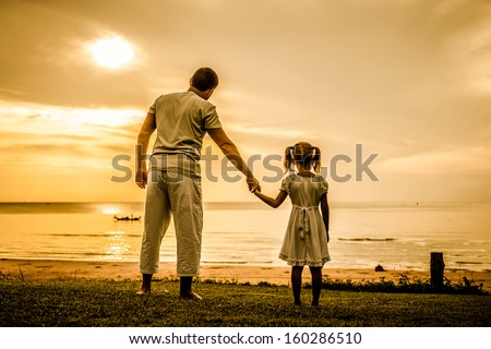 father and daughter standing at the beach in the dawn time - stock photo