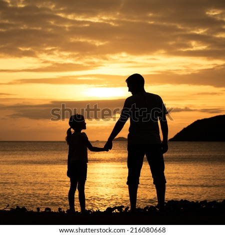 Father and daughter standing on the beach at the sunset time. - stock photo