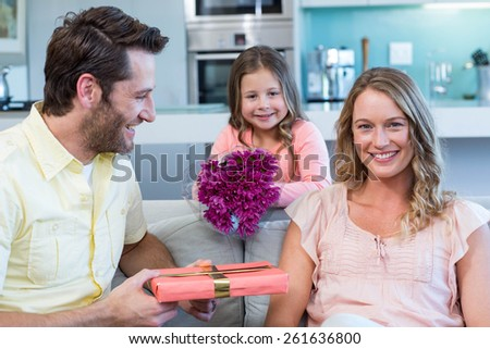 Father and daughter surprising mother with gift at home in the living room - stock photo