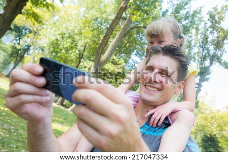 Father and Daughter Taking a Selfie - stock photo