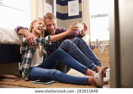 Father and daughter taking selfie together - stock photo