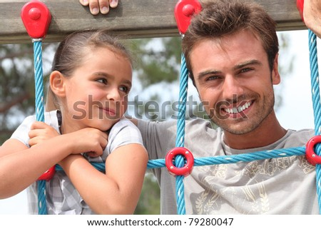 father and daughter together in the playground - stock photo