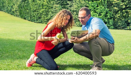 Father and daughter using netbook on the grass.