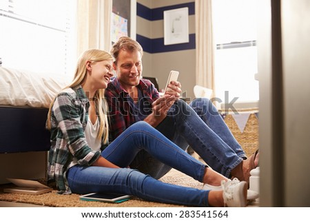 Father and daughter using smart phone together - stock photo