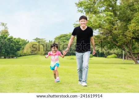 Father and daughter walking in park - stock photo