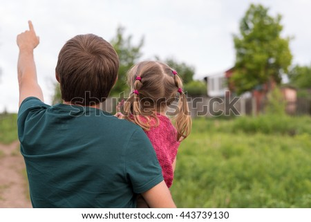 Father and daughter walking on a hill