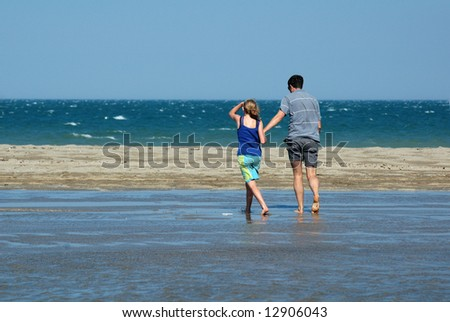 father and daughter walking on beach - stock photo