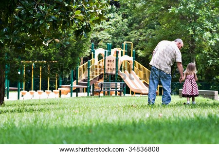 Father and daughter walking to the playground on a sunny day.